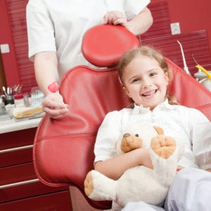 Young girl in a dental chair smiling